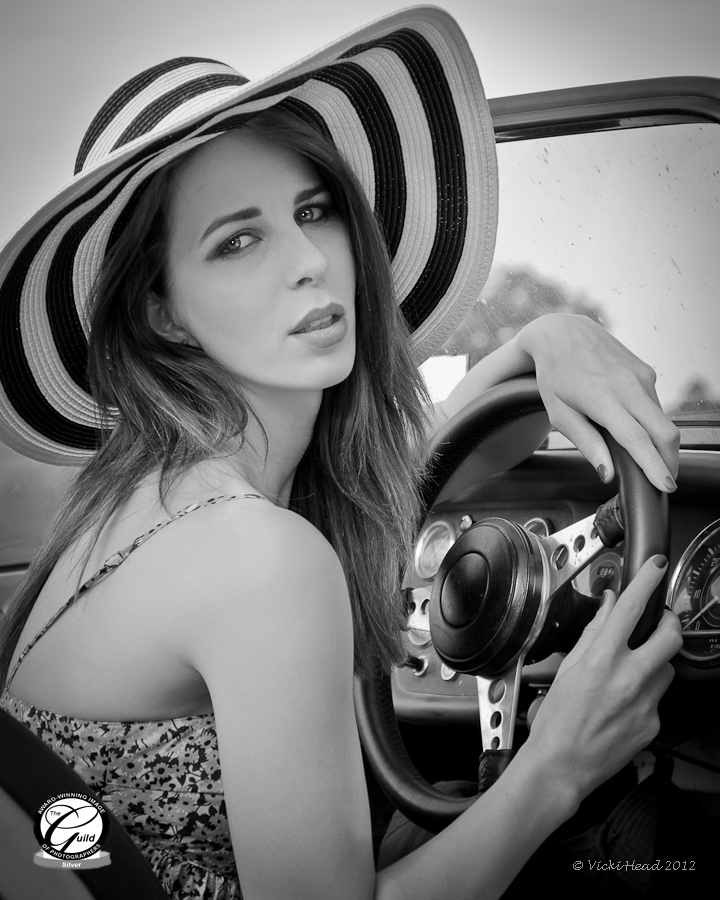 Black and white photograph of girl in a sports car