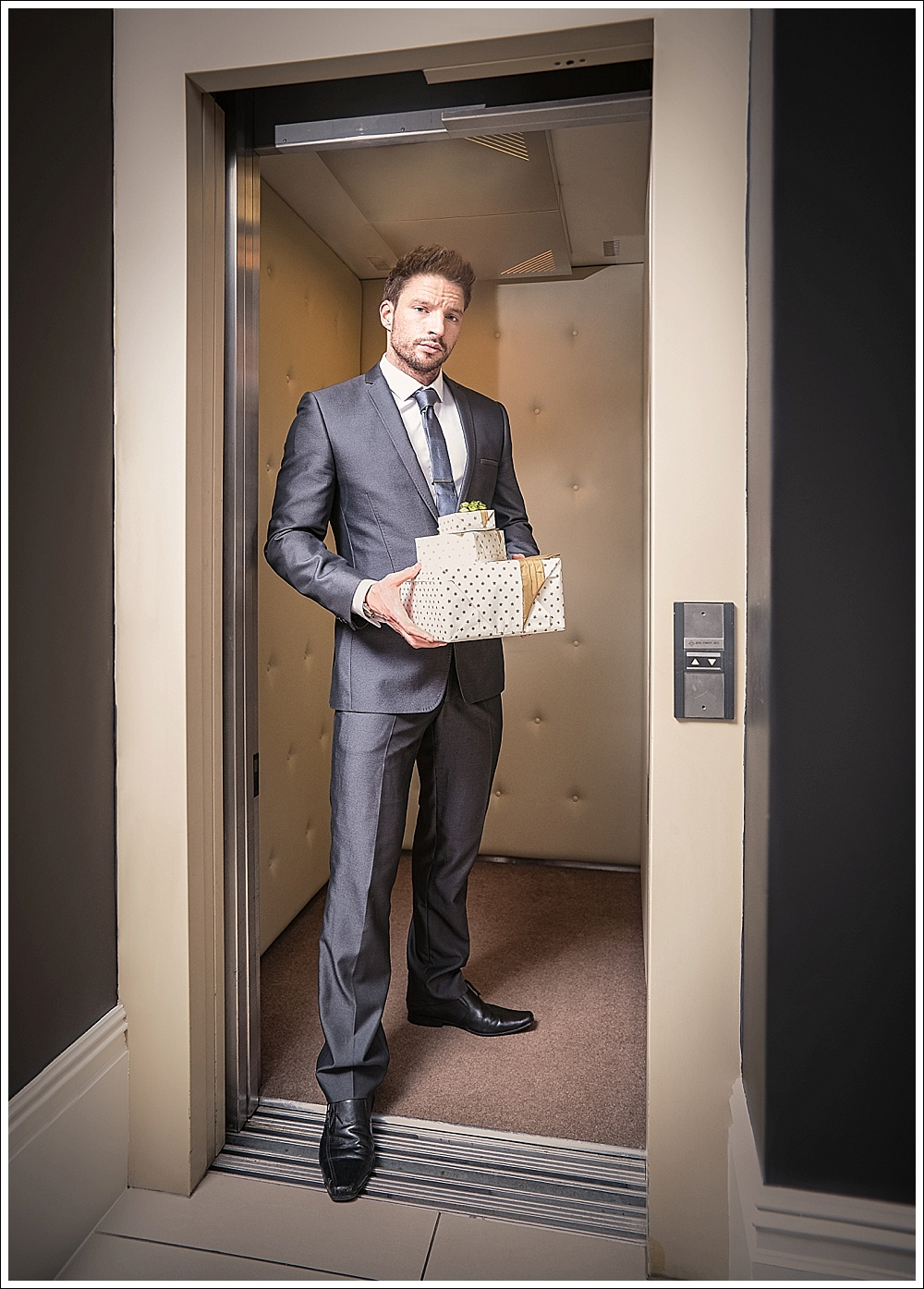 Male model in elevator with gifts
